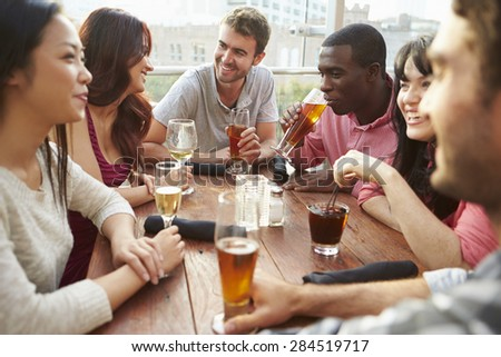 Group Of Friends Enjoying Drink At Outdoor Rooftop Bar - stock photo