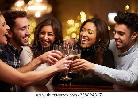 Group Of Friends Enjoying Evening Drinks In Bar - stock photo