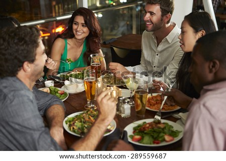 Group Of Friends Enjoying Evening Meal In Restaurant - stock photo