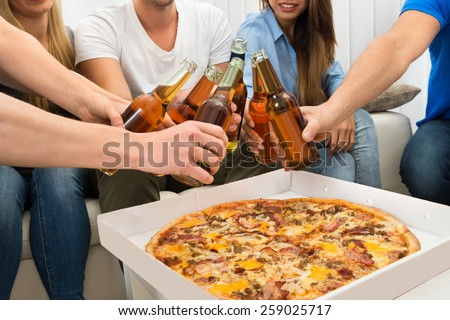Group Of Friends Enjoying Party With Pizza And Beer - stock photo