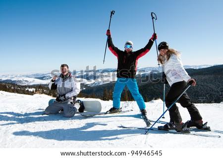 Group of friends enjoying skiing and snowboarding at a ski resort - stock photo