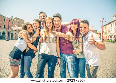 Group of friends grimacing in front of the camera - Young happy people having fun outdoors and posing for the camera - stock photo