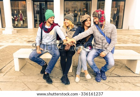 Group of friends hands on top - Teamwork students having fun outdoors - Two couples of young tourists sitting  in town square - Beautiful trendy models enjoying life - Concept of friendship and youth - stock photo