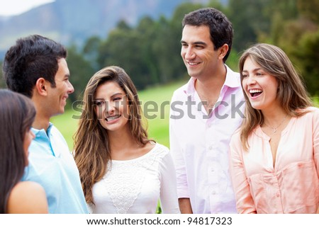 Group of friends hanging around outdoors and smiling - stock photo