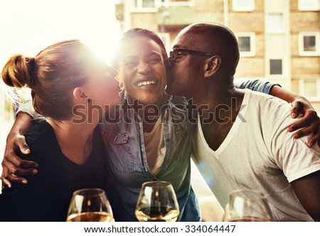 Group of friends having a good time kissing each other for fun - stock photo