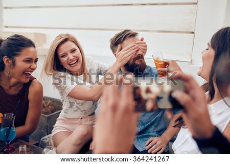 Group of friends having fun at a party with man taking a photo on a smart phone. Young people enjoying a party together. - stock photo