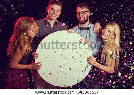 Group of friends having fun, celebrating New Year's Eve and holding a blank cardboard circle - stock photo