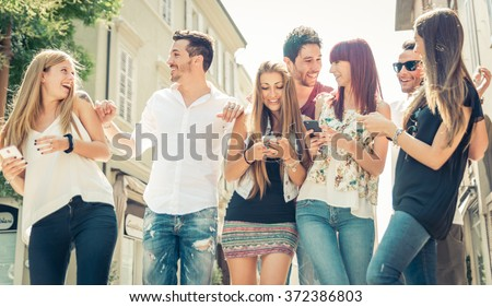 Group of friends having fun in the city center. Having fun and watching things on the smart phones - stock photo