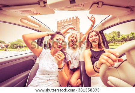 Group of friends having fun on the car. Singing and laughing in the city center - stock photo
