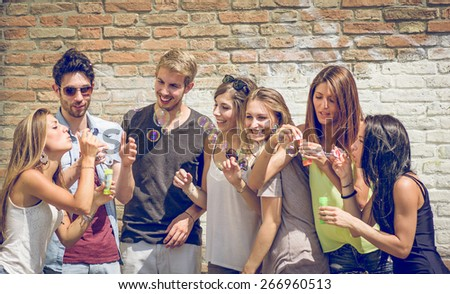group of friends having fun together and making soap bubbles. concept about friendship and people - stock photo