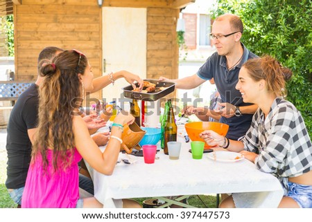 Group of friends having lunch together in the garden. A man is holding a tray with some sausages and bread slices. Happiness and lifestyle concepts, summer season. - stock photo