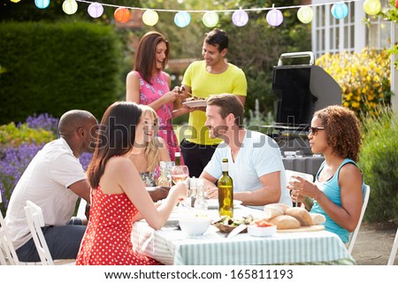 Group Of Friends Having Outdoor Barbeque At Home - stock photo
