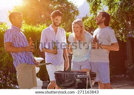 group of friends having outdoor garden barbecue laughing with alcoholic beer drinks - stock photo