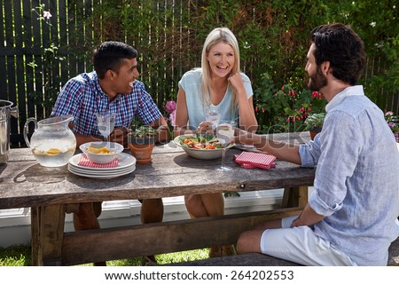 group of friends having outdoor garden cocktail dinner party - stock photo