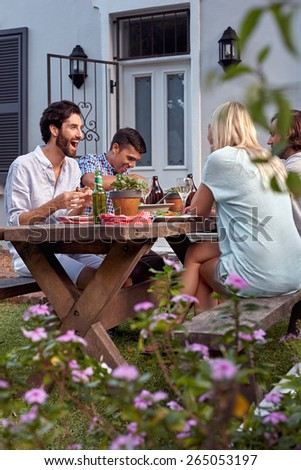 group of friends having outdoor garden dinner party with drinks - stock photo