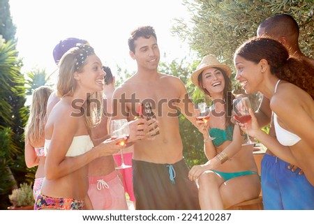 Group Of Friends Having Party By Swimming Pool - stock photo
