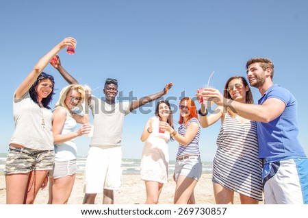 Group of friends having party on the beach - Some people drinking and dancing in a bar outdoors -Young playful people having fun and toasting drinks to celebrate - stock photo