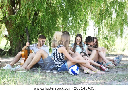 Group of friends having rest at park - stock photo