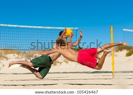 Group of friends � here two men to be seen - playing beach volleyball, they are jumping after the ball - stock photo