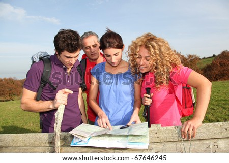 Group of friends hiking in countryside - stock photo