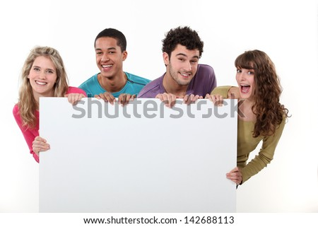 group of friends holding a blank poster - stock photo