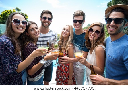 Group of friends holding a glass of cocktail on a sunny day - stock photo