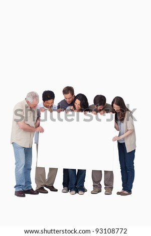 Group of friends holding blank sign together against a white background - stock photo