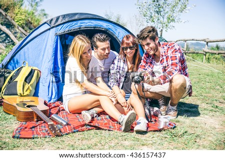 Group of friends in a campsite looking at picture done during the vacation - stock photo