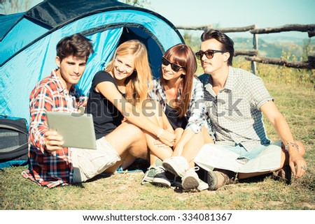 group of friends in a tent watching the map during a rainy day - stock photo