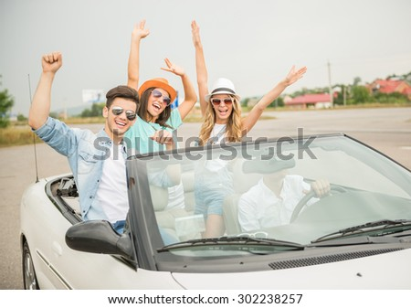 Group of friends in sunglasses traveling on the white cabriolet and having fun. - stock photo