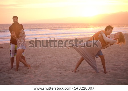 Group of Friends in their twenties dancing on the Beach at Sunset in Venice Beach California - stock photo