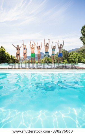 Group of friends jumping at poolside with their hands raised - stock photo