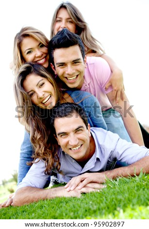 Group of friends lying outdoors on top of each other having fun - stock photo