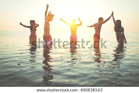 Group of friends making party in the water at sunrise time - stock photo