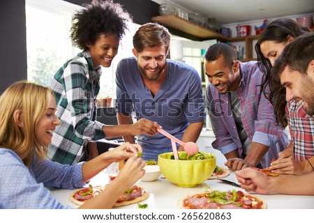 Group Of Friends Making Pizza In Kitchen Together - stock photo