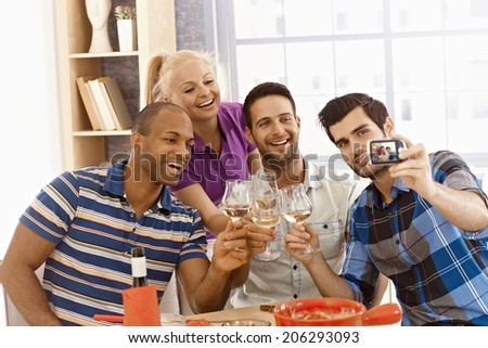 Group of friends making self portrait of themselves, smiling happy, drinking at home. - stock photo