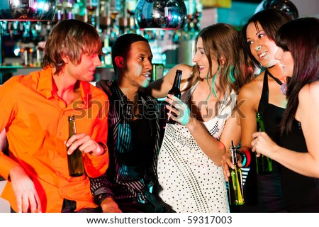 Group of friends - men and women of different ethnicity - having fun in a disco or nightclub - stock photo