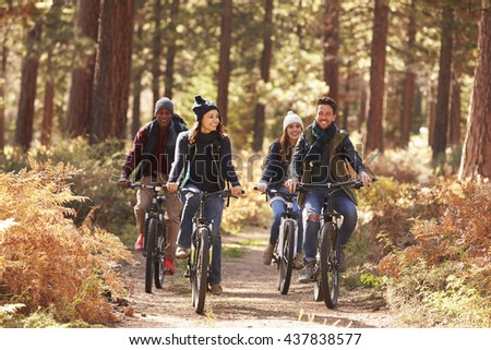 Group of friends on bikes in forest front view - stock photo