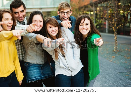 Group of friends outside pointing and smiling - stock photo