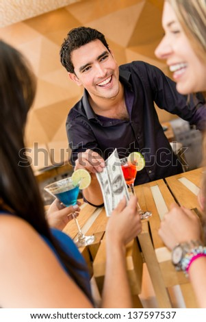 Group of friends paying for drinks at the bar with cash - stock photo