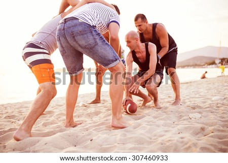 Group Of Friends playing Football On Beach Together. Depth of field, selective focus - stock photo