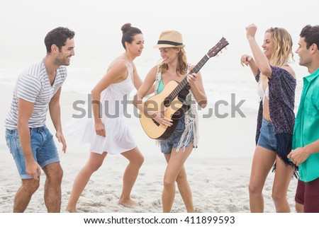 Group of friends playing guitar and dancing on the beach - stock photo