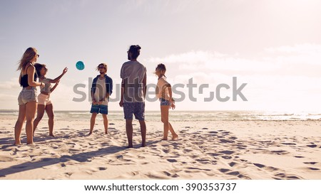 Group of friends playing with ball at beach on a summer day. Young men and woman on sandy beach playing a game of passing the ball. - stock photo