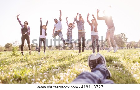 Group of friends running happily together in the grass and jumping - stock photo