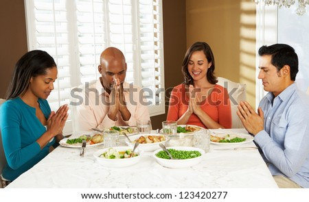 Group Of Friends Saying Grace Before Meal At Home - stock photo