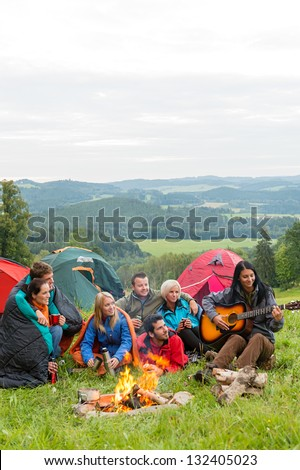 Group of friends sitting beside tents, campfire girl playing guitar - stock photo