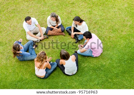 Group of friends sitting down in a circle outdoors - stock photo