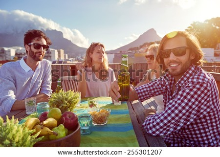 Group of friends sitting hanging out with drinks on the rooftop - stock photo