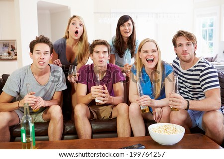 Group Of Friends Sitting On Sofa Watching Sport Together - stock photo