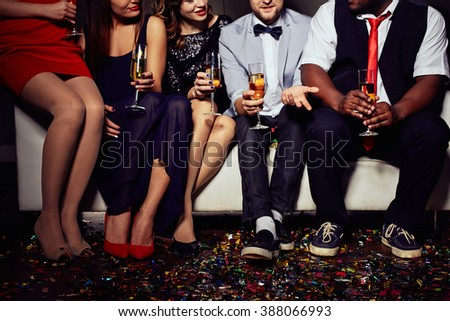 Group of friends sitting together with flutes of champagne - stock photo